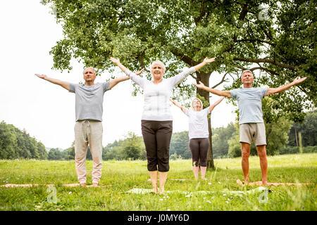 Vier Menschen, die Yoga in das Feld ein. - Stockfoto