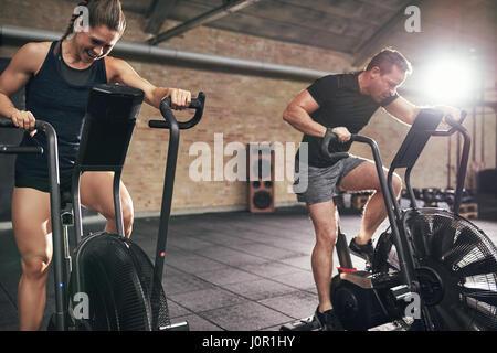 Junger Mann und Frau zäh Reiten auf Radfahren Maschinen im modernen Fitnessraum. - Stockfoto