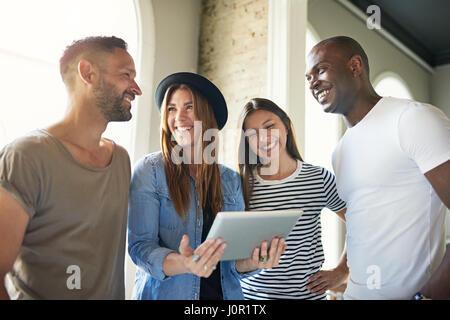 Gruppe von vier jungen stilvolle Freunde lachen und gerade etwas auf Tablet in hellen, modernen Zimmer. - Stockfoto