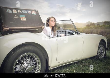 Blonde Frau, die aus Auto - Stockfoto