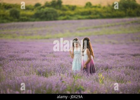 Zwei Mädchen stehen in einem Lavendelfeld, Stara Zagora, Bulgarien - Stockfoto