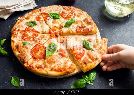 Menschen Hand die Scheibe der Pizza Margherita. Pizza Margarita und Kinderhand hautnah. - Stockfoto
