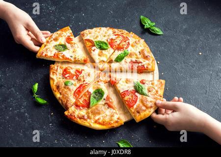 Menschen Hände nehmen Scheiben der Pizza Margherita. Pizza Margarita und Hände hautnah auf schwarzem Hintergrund. - Stockfoto