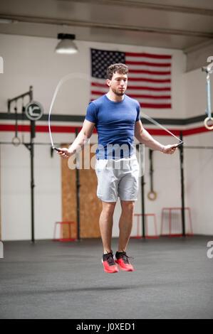 Passen Sie sportlicheren jungen Mann mit einem Springseil um zu trainieren in einer Crossfit Gym springen Luft in - Stockfoto