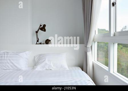 moderne Lampe auf hölzerne Nachttisch in weißen modernen Schlafzimmer, Innenarchitektur - Stockfoto