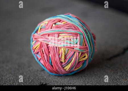 Ball gemacht von farbigen Gummibändern. Schwarzem Schaumstoff. Auf schwarzem Hintergrund isoliert. - Stockfoto