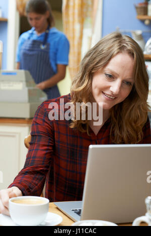 Frau In Coffee-Shop mit Laptop-Computer - Stockfoto
