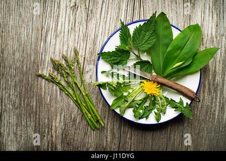 Frühling Essen Brennnessel, Löwenzahn, Bärlauch und Spargel auf hölzernen Hintergrund - Stockfoto
