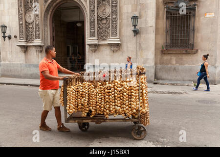 Eine kubanische Mann verkaufen Zwiebeln aus einem mobilen Wagen in Havanna, Kuba. - Stockfoto