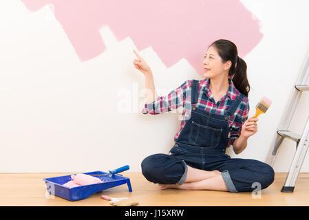 ... Frau Mit Pinsel Auftragen Rosa Farbe An Der Wand Und Zeigt  Präsentieren. Multikulturelle Chinesische Asiatin