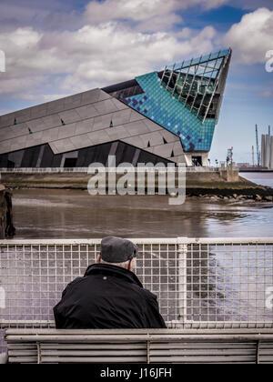 Alter Mann tragen flache Kappe sitzen auf Bank mit Blick auf Wasser, The Deep, Besucherattraktion, Hull, UK. - Stockfoto