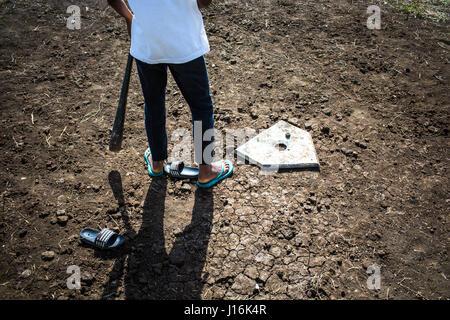 Ein Junge trägt Flip Flops und mit einem Baseballschläger steht zu Hause Basis auf einem Dirt-Feld - Stockfoto