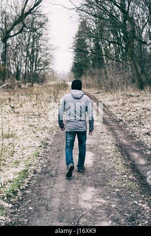 Rückansicht des ein Mann zu Fuß auf einer Land-Straße - Stockfoto