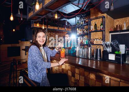 Eine Besucher Mädchen Lächeln in der Bar mit Cocktails - Stockfoto