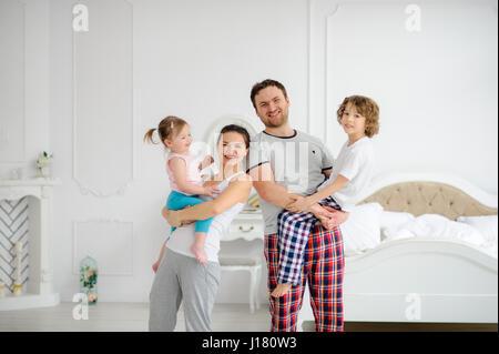 Fröhlicher Beginn des Tages in einer glücklichen Familie. Gemütliches Schlafzimmer. Junge Eltern halten die Hände - Stockfoto