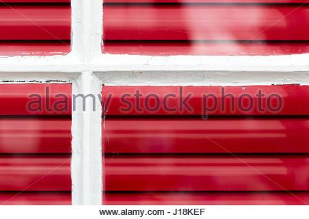 Blick auf ein Fenster mit leuchtend rote horizontale Jalousien innen, Hamble le Rice, Hampshire - Stockfoto