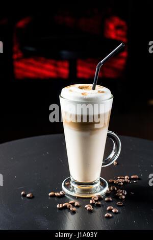 Ausgefallene Latte, die in Glas auf dem schwarzen Tisch Kaffee - Stockfoto