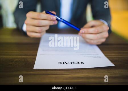 Geschäftsmann oder Arbeitsuchende überprüfen Sie seinen Lebenslauf auf seinem Schreibtisch vor dem Senden an einen - Stockfoto
