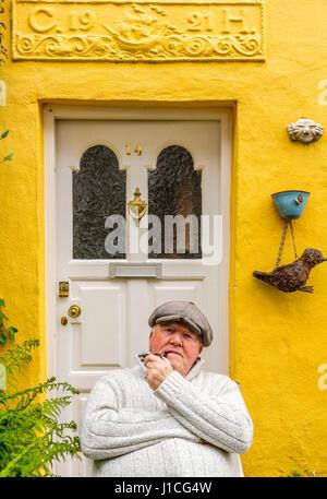 Clovelly, Devon, England, A Wohnsitz in diesem malerischen Dorf in Nord-Devon genießt draußen seine bunt bemalte - Stockfoto