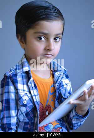 Intelligentes Kind hält einen Tablet-Computer mit Blick auf das Objektiv der Kamera - Stockfoto