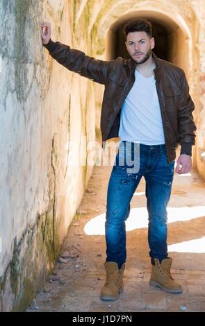 Gut aussehender Mann in Lederjacke posiert in einem tunnel - Stockfoto