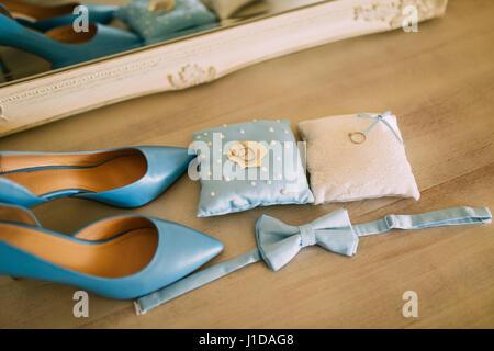 491843e1abc5b0 ... Hochzeitsschuhe einer Braut auf einem Stein Hintergrund und eine blaue  Brautstrauß - Stockfoto