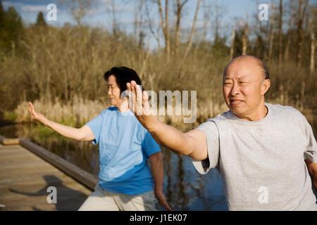 Ein Schuss von einem senior asiatischen paar üben Tai Chi Übung - Stockfoto