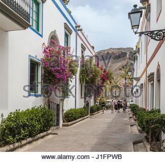 Malerische Blumen Avenue Atr Puerto de Mogan mit Touristen auf Gran Canaria, einer der spanischen Kanarischen Inseln - Stockfoto