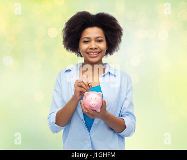 glücklich Afrikanerin, Münze ins Sparschwein - Stockfoto