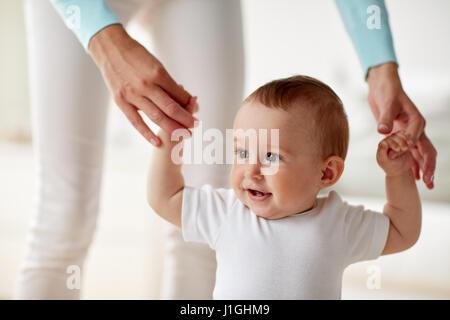glückliches Baby mit Mutter Hilfe laufen lernen - Stockfoto