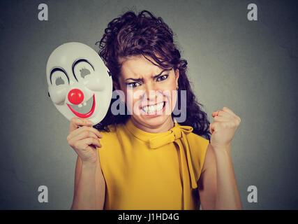 Porträt wütend schreiende Frau Ausziehen eine Clownsmaske mit dem Ausdruck Glück auf graue Wand Hintergrund isoliert. - Stockfoto