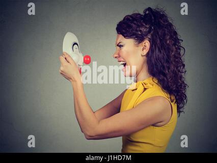 Seitenansicht einer wütenden jungen Frau schreiend auf happy Clownsmaske auf grauem Hintergrund isoliert - Stockfoto