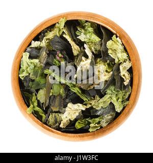 Getrocknete Algen Flocken in Holzschale. Mischung aus Meeressalat, Wakame und Nori. Essbare Grüne Algen und Seegras. - Stockfoto