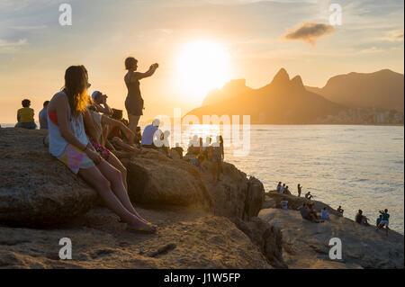 RIO DE JANEIRO - drängeln sich Menschen auf den Felsen am Arpoador für Position, um den Sonnenuntergang bei zwei - Stockfoto