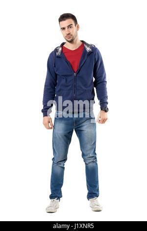 Angespannte lässig Jüngling in blaues Sweatshirt mit Kapuze, Blick in die Kamera skeptisch. Ganzkörper-Länge-Porträt - Stockfoto