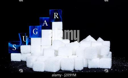 Mosaik Fliesen mit Buchstaben und Zucker Würfel vor schwarzem Hintergrund - Stockfoto
