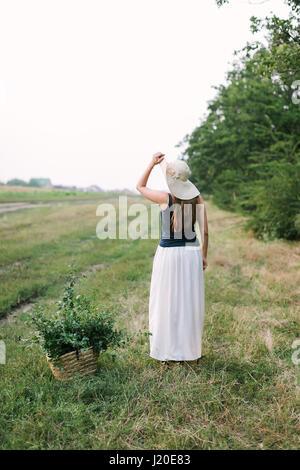 Menschen, Reisen und Natur Konzept - schöne Frau in ausgefallenen Kleidern und eleganten Hut posiert mit Rücken - Stockfoto