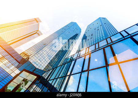 Moderne Wolkenkratzer im Geschäftsviertel in schönen goldenen Abendlicht bei Sonnenuntergang mit monochromen Retro-Vintage-Filter im niedrigen Weitwinkel Stockfoto