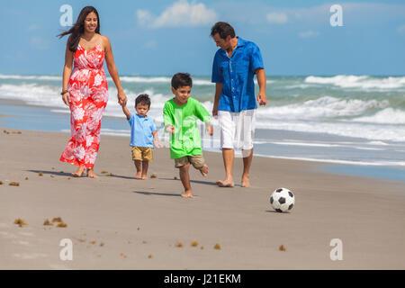 Eine glückliche Familie Mutter, Vater Eltern & zwei jungen Sohn Kinder, Playng Fußball oder Fußball und Spaß im - Stockfoto