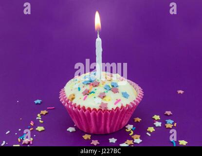 Hell lila Hintergrund mit einzelnen weißen Tasse Kuchen bei rosa Papier und zündete die Kerze mit Farbe Sterne Streusel - Stockfoto