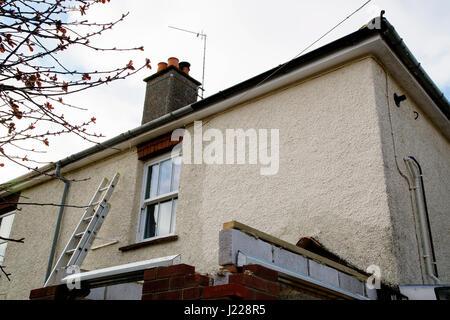 Sanierung In Arbeit auf eine Doppelhaushälfte mit gerenderten Fassade und Veranda Teil gebaut. Eine Leiter lehnt - Stockfoto