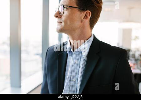 Zugeschnittenen Schuss von reifer Geschäftsmann im Büro stehen. Kaukasische männliche Führungskraft in Anzug und - Stockfoto