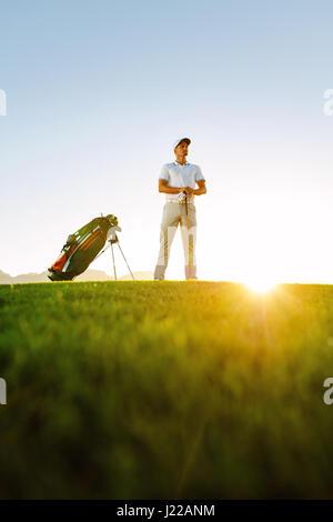 Niedrigen Winkel Schuss von Profi-Golfer bei Sonnenuntergang auf Feld stehen. Junger Mann Golfen auf dem Golfplatz. - Stockfoto