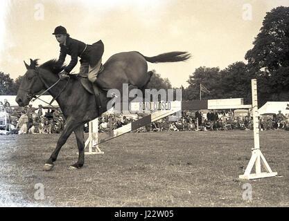 In den 1950er Jahren springt ein Springreiter auf der Horse Show auf der Bucks County Show, England, Großbritannien, - Stockfoto