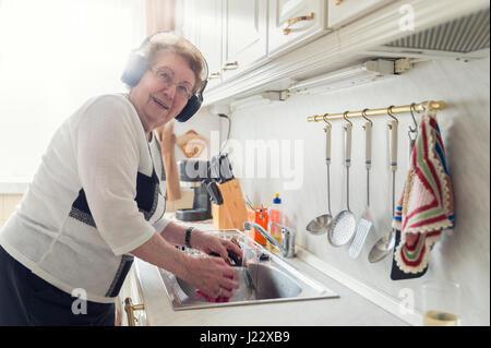 Porträt von senior Frau Musik hören mit Kopfhörern beim Abwasch - Stockfoto