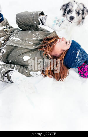 Junge Frau mit ihrem Border Collie im Schnee spielen - Stockfoto