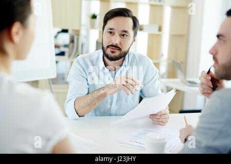 Porträt von asiatischen bärtige lauschte während der Diskussion Geschäft mit Kollegen während der Sitzung im modernen - Stockfoto