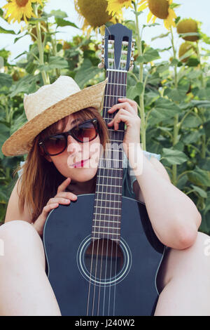 Junges Land Frau mit ihrer schwarzen Gitarre - Stockfoto