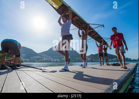 RIO DE JANEIRO - 30. Januar 2016: Gruppe von brasilianischen Ruderer tragen ihr Boot von der Anlegestelle nach einem - Stockfoto