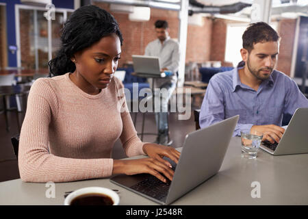Geschäftsleute, die Arbeit an Laptops im Büro-Kaffee-Bar - Stockfoto